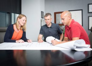 Real estate developers sit at a table with blueprints discussing development plans.